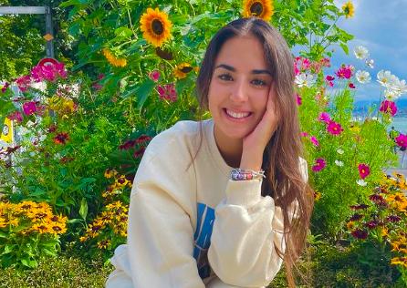 Laura López posando con una sudadera frente a un paisaje de flores amarillas y rosas